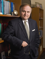 Nicholas Peppas standing in office with arm resting on bookshelf