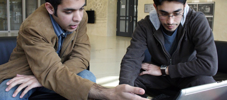 two students sitting and looking at computer screen in lobby of building